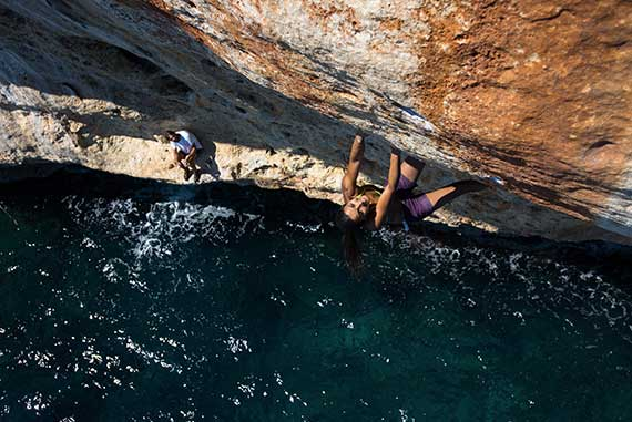 Climb above water in Majorca. Deep water solo. Vertical sailing tour